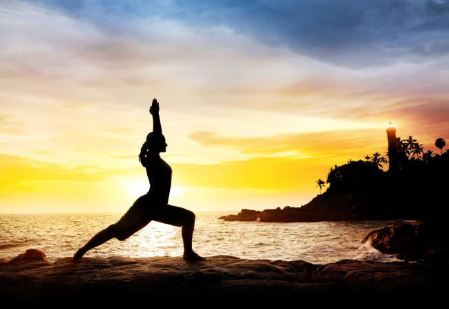 Woman doing Yoga warrior pose in silhouette on the cliff near lighthouse at sunset sky in Kovalam, Kerala, India